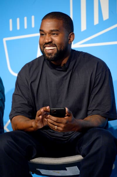 Kanye West is smiling!  Wow!