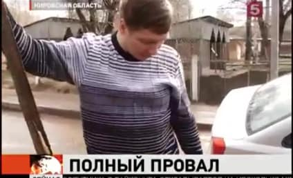 Russian Taxi Driver Tries, Fails to Free Car From Pothole