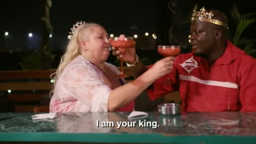 Angela Deem and Michael Ilesanmi cross arms and drink in crowns