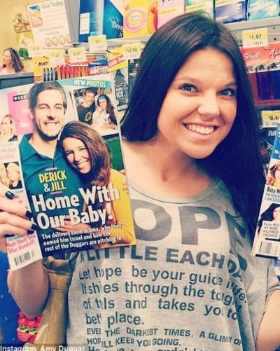 Amy Duggar Holds Tabloid