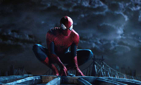 Spiderman crouched on a roof.