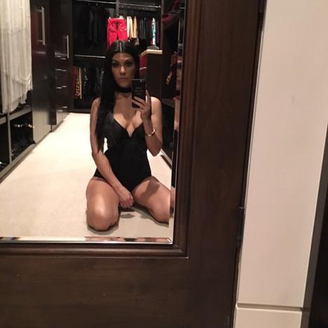 Kourtney Kardashian kneeling in black leotard